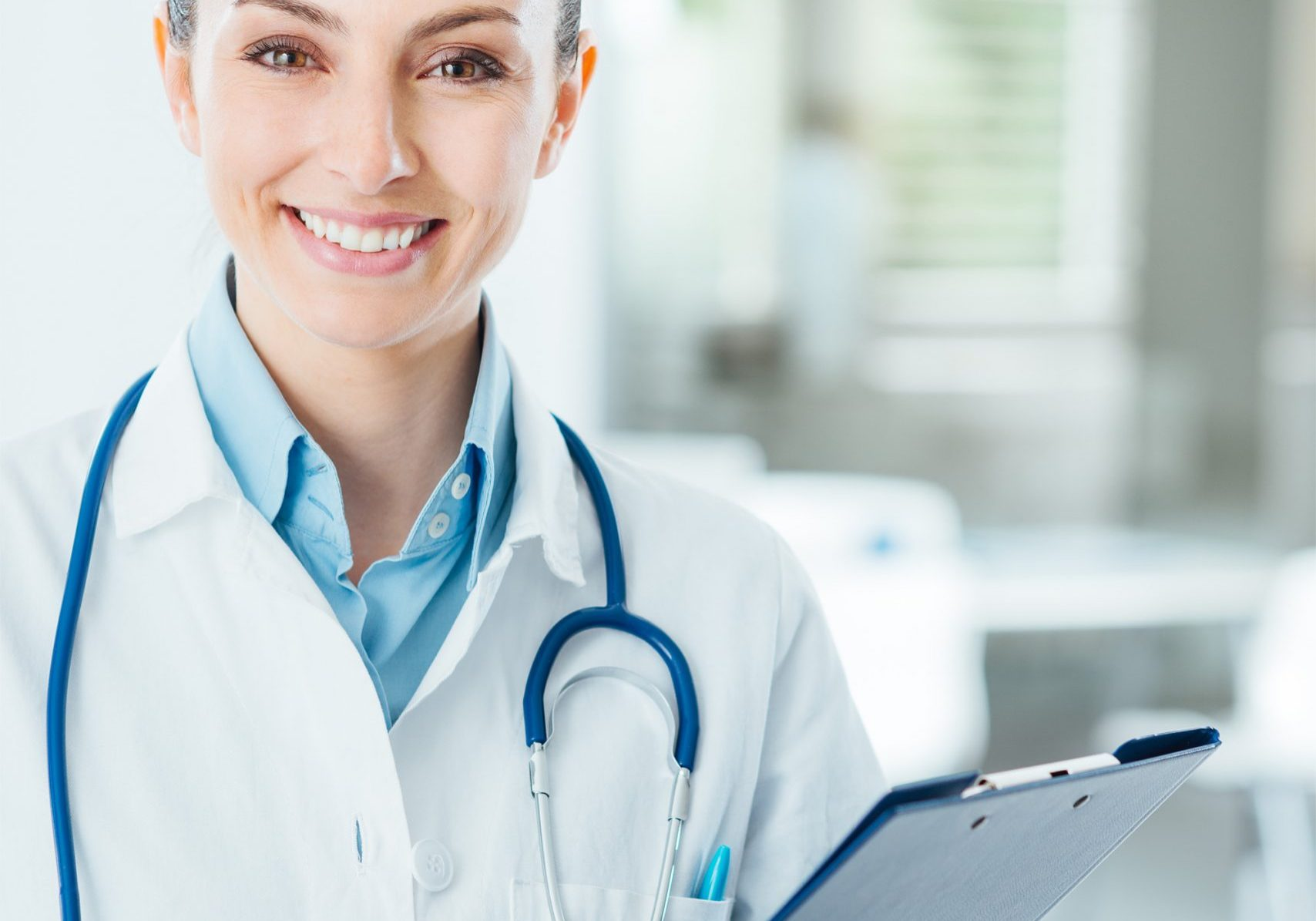 Smiling female doctor with lab coat in her office holding a clipboard with medical records, she is looking at camera